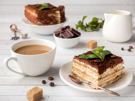 Tiramisu Dessert with Mint and Cup of Coffee on White Wooden Table.