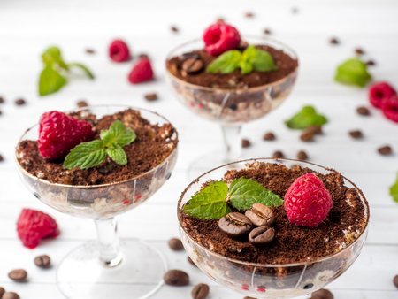 Dessert Tiramisu in glass goblet with mint coffee beans and fresh raspberries on white wooden table.