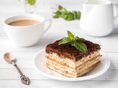 Tiramisu Dessert with Mint and Cup of Coffee on White Wooden Table. 免版税图像 - 92927842