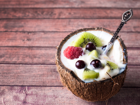 Fruit Yogurt in the Coconut halves with Fresh Berries on a Dark Wooden Background Stock Photo