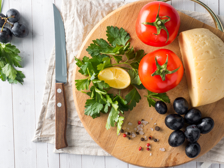 Piece of cheese with parsley, tomatoes grapes on a cutting Board with a knife.