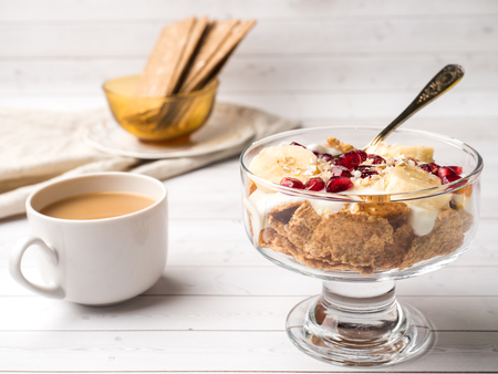 Glass bowl with muesli and yogurt with banana, pomegranate seeds.