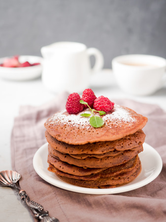 Chocolate pancakes with powdered sugar raspberry on light background
