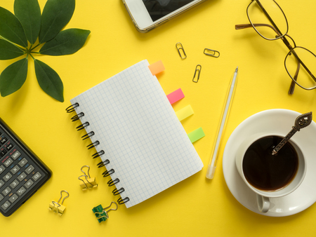 Business flat lay with copy space, calculator, pencil, Notepad, coffee glasses on colorful yellow background