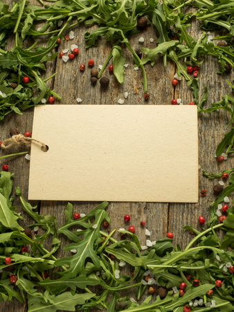 Blank note on wooden background with leaves of arugula, red and black pepper salt 版權商用圖片