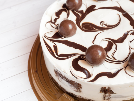 Delicious easy ice cream cake with chocolate on a light background.