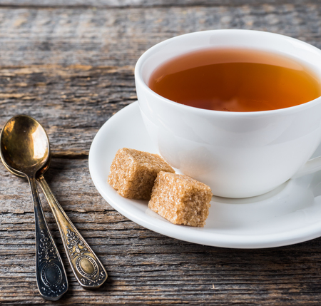 White tea Cup and saucer brown cane sugar on a rustic wooden background.