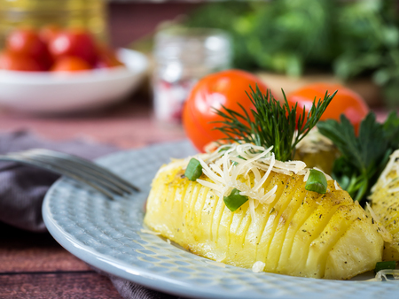 Baked potato with vegetables tomatoes pepper green onion parsley on plate, selective focus.