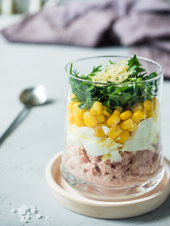 Fresh tuna salad with egg corn greens in a glass Cup on a concrete table. copy space. Stock Photo