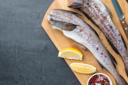 Slave raw Fish on wooden cutting Board on dark background.