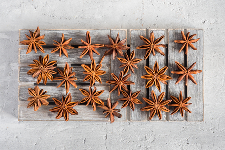 Spicy spice star anise on wooden stand on grey concrete background.