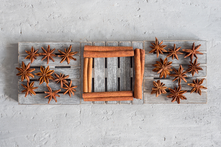 Spicy spice cinnamon sticks star anise on wooden stand on grey concrete background.