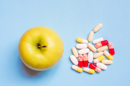 Different pharmaceutical pills and fresh green Apple on blue background.