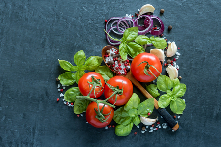 Tomatoes Basil Garlic and spices on a stone table in the form of heart healthy food Concept