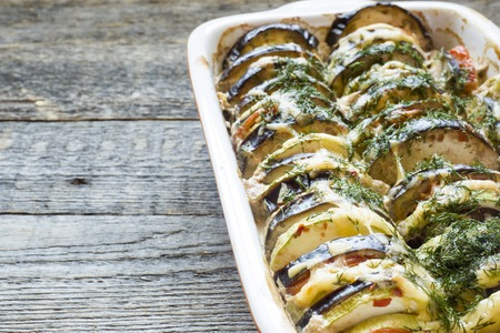 Grilled vegetables Zucchini Eggplant Tomato a Kind of Ratatouille on a rustic wooden background.