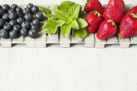 Fresh berries strawberries blueberries mint on a wooden stand, grey background with Copy space for text.