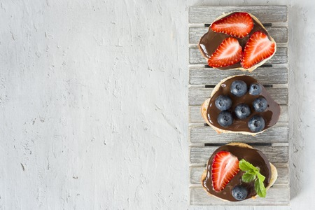 Toast bread with chocolate spread and berries strawberries blueberries mint on a wooden stand table grey. Copy space