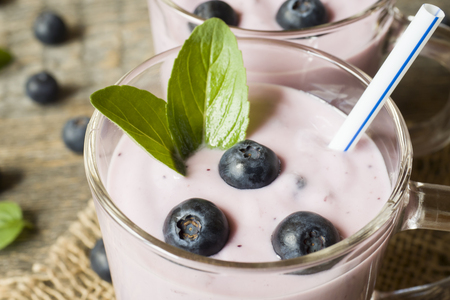 Blueberry yogurt in glass cups with fresh blueberries and mint on a wooden rustic table. Stok Fotoğraf