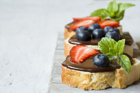 Toast bread with chocolate spread and berries strawberries blueberries mint on a wooden stand table grey. Stockfoto