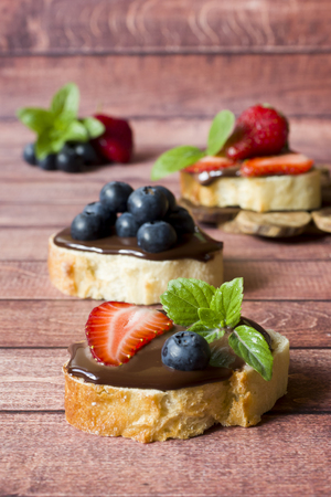 Toast bread with chocolate paste and strawberries blueberries mint on the table. Copy space