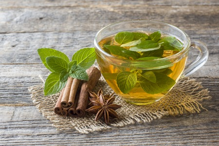 Cup of tea with fresh mint leaves and cinnamon anise on a wooden background. Copy space.