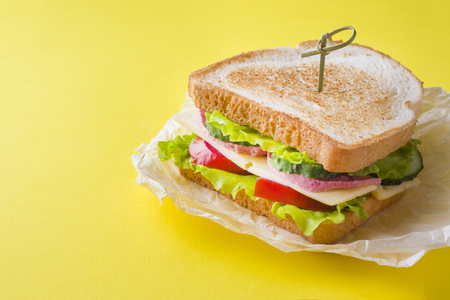 Sandwich with cheese, ham and fresh vegetables on a yellow bright background