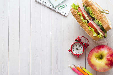 Snack for school with sandwich, fresh Apple and orange juice. Colorful school supplies. Copy space Stockfoto