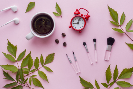Make-up brushes, a Cup of coffee and clock on pink pastel background. Beauty concept Stock Photo