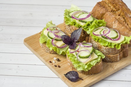 Open sandwiches with cheese, cucumbers and onions on wheat bread. Selective focus Stock Photo