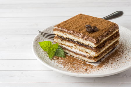 Delicious Tiramisu cake with coffee beans and fresh mint on a plate on a light background.