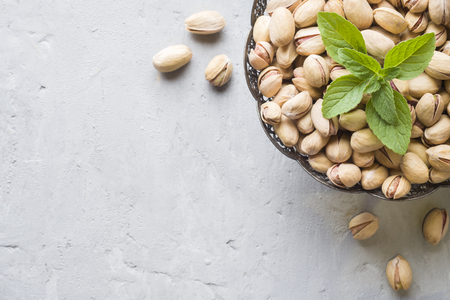 Delicious salted pistachios and fresh mint leaves on wooden background Archivio Fotografico