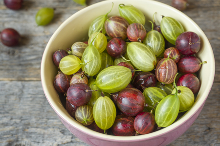 Gooseberry berries are red and white in a plate on a wooden rustic background