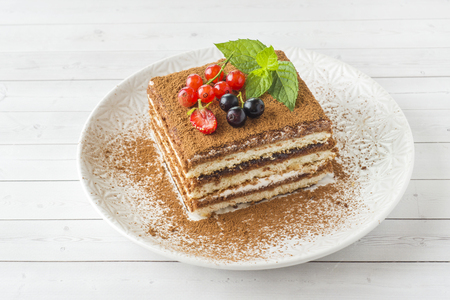 Delicious Tiramisu cake with fresh berries and mint on a plate on a light background