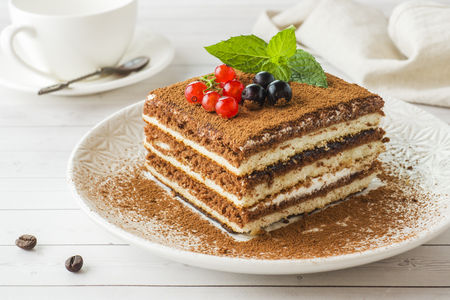 Delicious Tiramisu cake with fresh berries and mint on a plate on a light background. Breakfast with a Cup of coffee