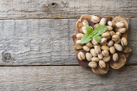 Delicious salted pistachios and fresh mint leaves on wooden background Reklamní fotografie