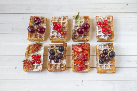 Homemade waffles with summer berries on a light table. Selective focus.