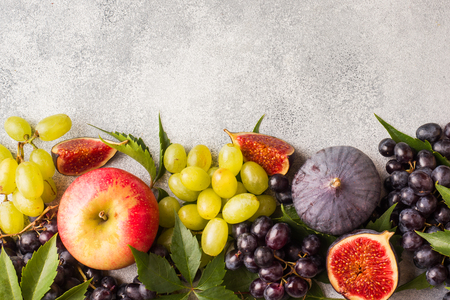 Frame of fresh autumn fruits. Grapes black and green, figs and leaves on a grey table with copy space