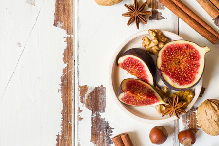 Fig walnuts cinnamon anise on a plate of old wooden background