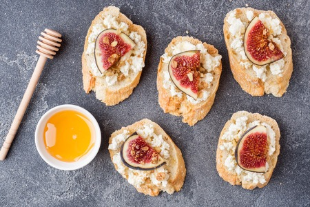 Snacks bruschetta with cottage cheese, walnut and honey and figs on a dark background.