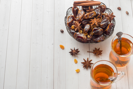 Oriental sweets, dried fruit dates and raisins, cinnamon and star anise in a plate. Turkish tea in glasses on a wooden background