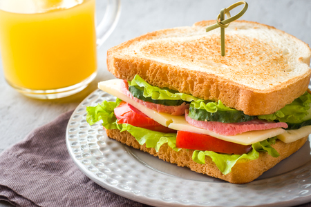 Sandwich with cheese, ham and fresh vegetables on a plate. Fresh juice and a Cup of coffee. The concept of Breakfast