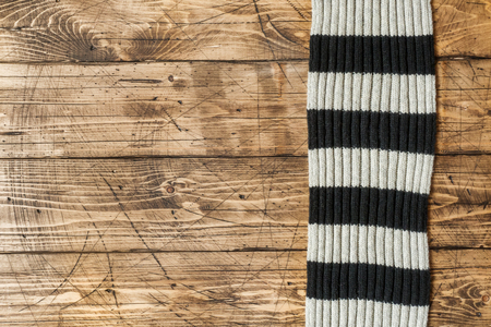 Striped wool scarf on brown wood background.