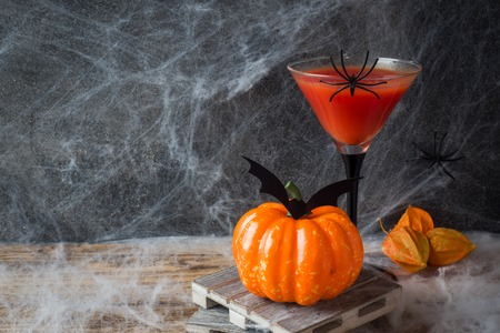 Bloody Mary cocktail, pumpkin with bats and spiders for Halloween, selective focus. Copy space