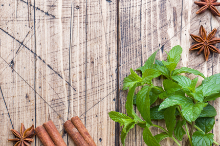Green fresh mint, spices cinnamon and anise on wooden table, copy space.