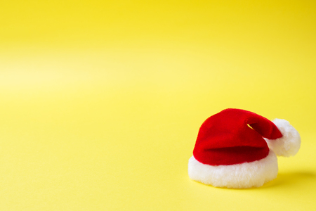 Christmas new year concept. Santa's red hat on yellow Stock Photo
