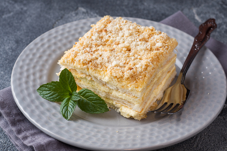 Layered cake with cream Napoleon millefeuille vanilla slice with mint on dark background