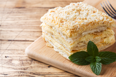 Layered cake with cream Napoleon millefeuille vanilla slice with mint on wooden background Stock Photo