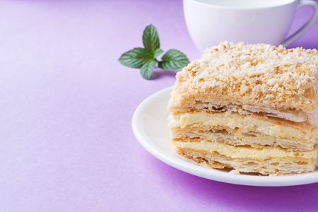 Puff cake with cream Napoleon Millefeuille vanilla slice with mint color on purple background Stock Photo