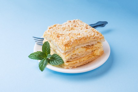 Layer cake with cream Napoleon millefeuille vanilla slice with mint on a colored blue background