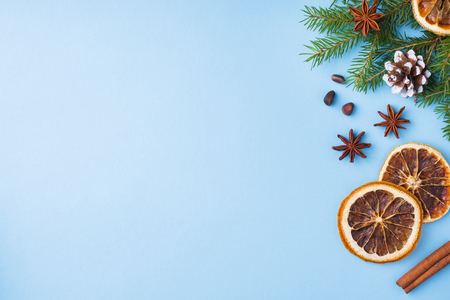 Decoration for Christmas concept. Food oranges nuts spices pine cones Christmas tree on blue pastel background with copy space